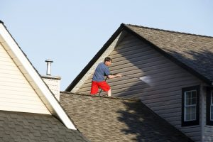 Man on steep roof with pressure washing equipment