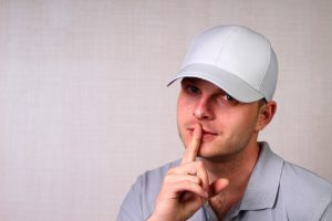 man in a baseball cap with his index finger pressed to his lips